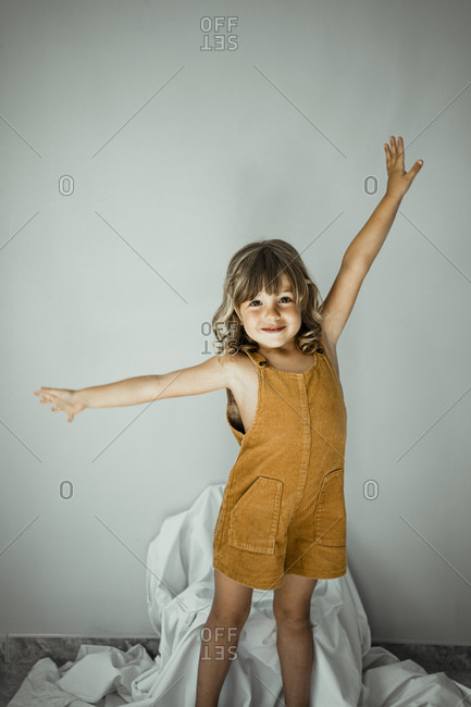 Cute girl with arms outstretched standing against wall at home