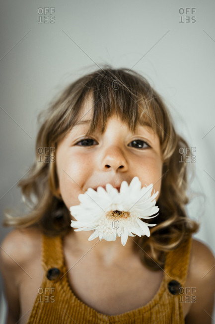 Cute girl carrying flower in mouth against wall at home