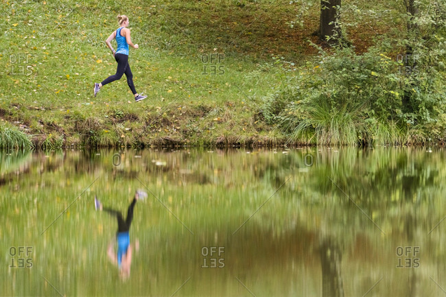 Reflection of young female athlete jogging in forest