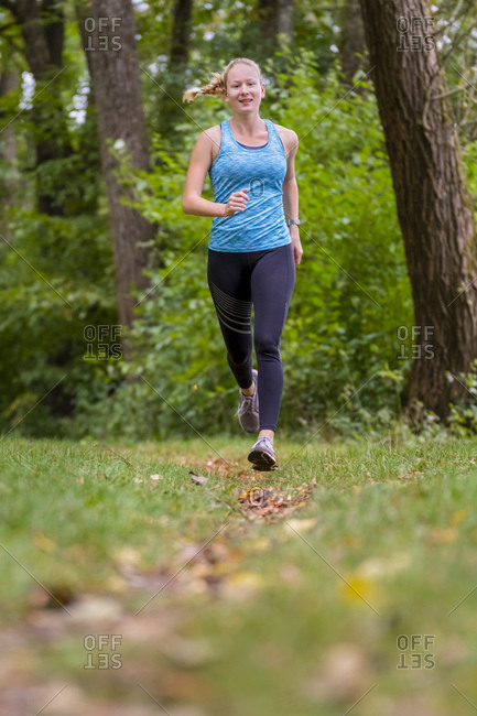 Active female athlete jogging in forest