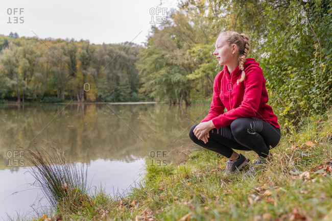 Female athlete crouching while looking at lake in forest