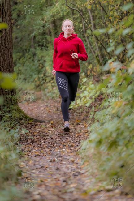 Determinant female athlete jogging in forest