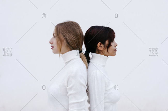 Female friends in turtleneck shirts standing back to back against white background