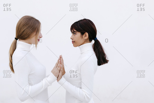 Young women touching hands while looking at each other against white background