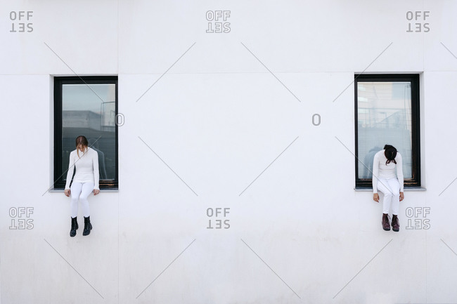 Sad young women sitting on windows of white building during coronavirus pandemic
