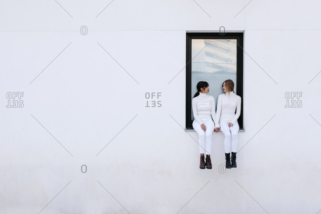Young women looking at each other while sitting on window of white building