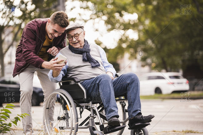 Senior man in wheelchair and his adult grandson looking together at smartphone