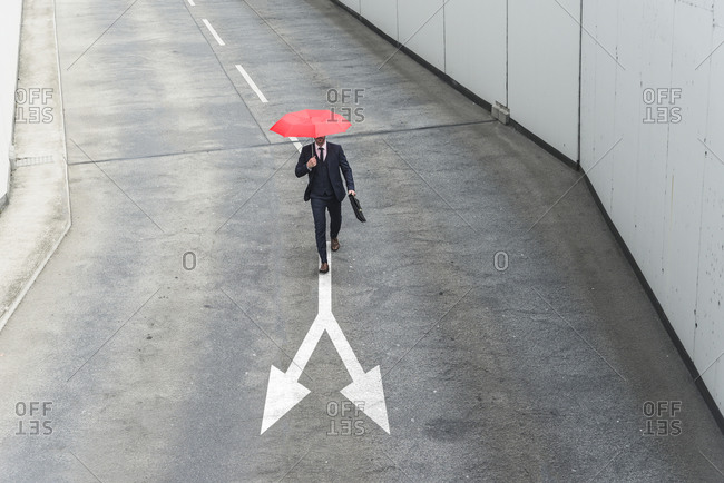 Businessman with red umbrella walking on road marking