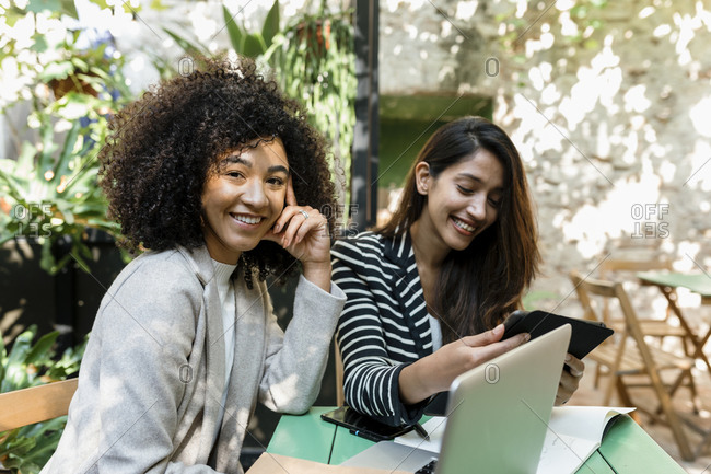 Smiling female coworkers smiling using laptop and digital tablet sitting in cafe
