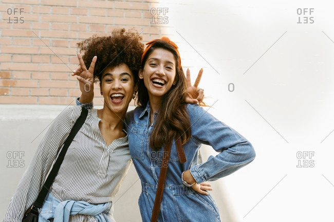 Carefree friends showing peace sign while standing against wall