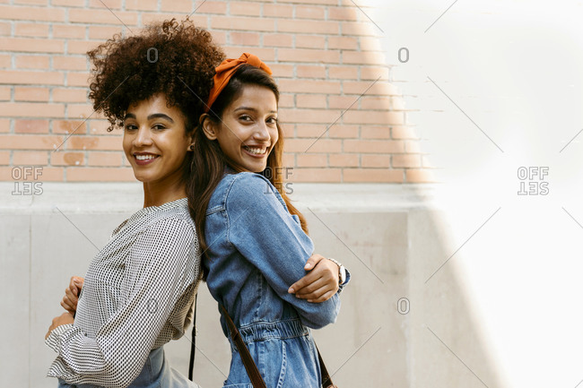 Smiling friends standing back to back against wall