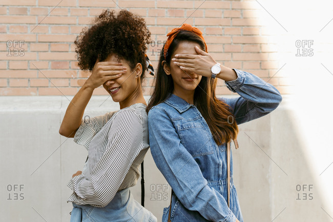 Female friends covering eyes while standing back to back against wall