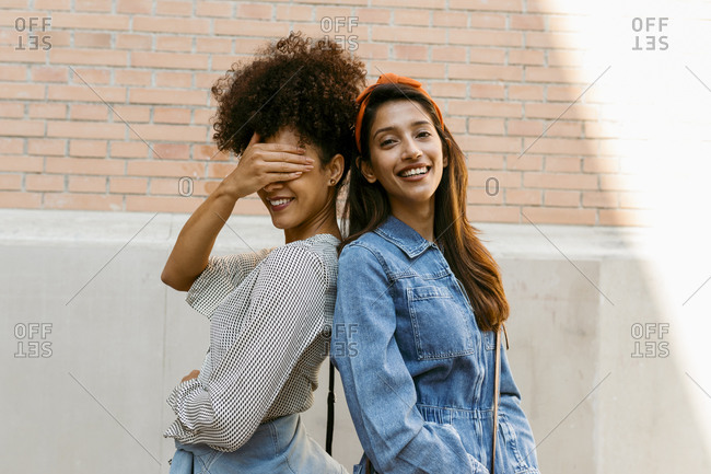 Friend covering eye with hand while standing back to back with woman against wall