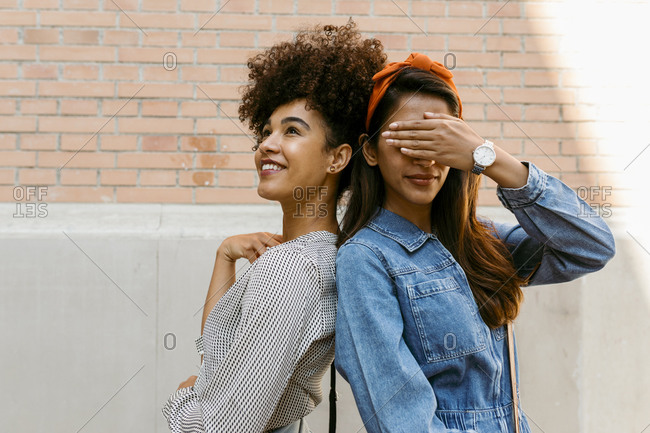 Young woman covering eye with hand while standing back to back with friend against wall