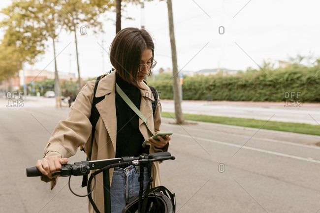 Mid adult woman using mobile phone while standing with electric push scooter on road