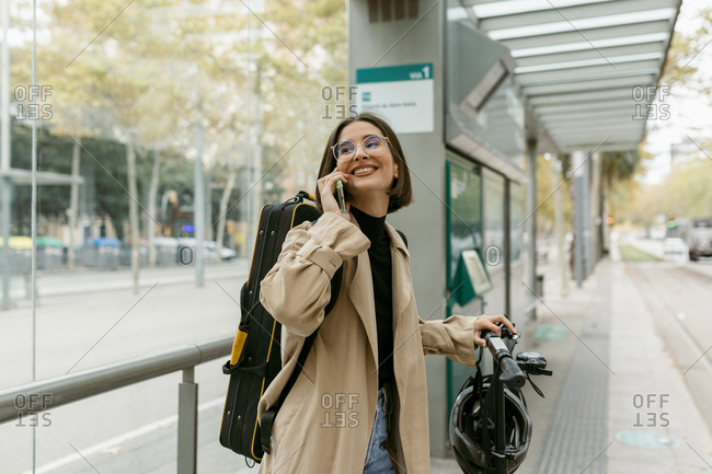 Smiling woman talking on mobile phone while standing at tram station in city
