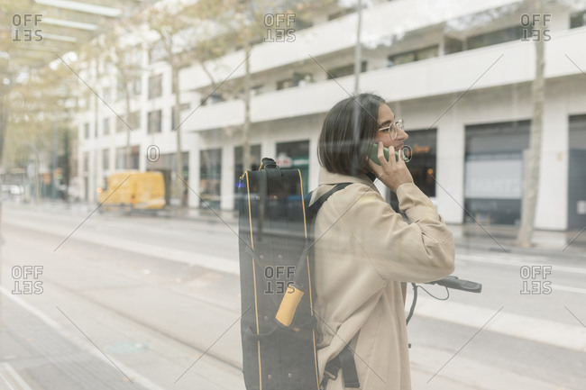 Woman with instrument case talking on mobile phone while standing at tram station in city