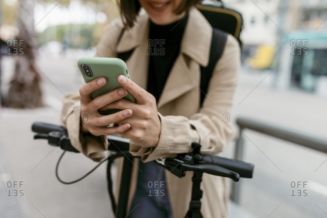 Woman using smart phone while standing with electric push scooter on road
