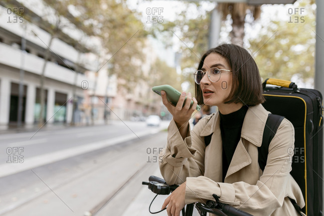 Beautiful woman with instrument case and electric push scooter talking on mobile phone while standing at city