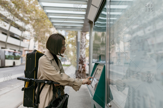 Woman with instrument case using ticket machine while standing with electric push scooter at tram station in city