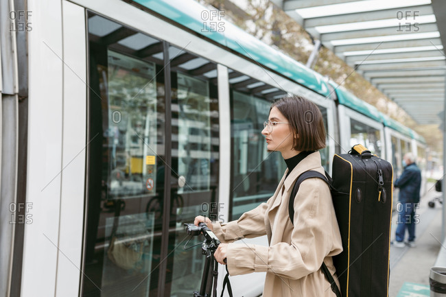 Woman with instrument case and electric push scooter standing by tram in city
