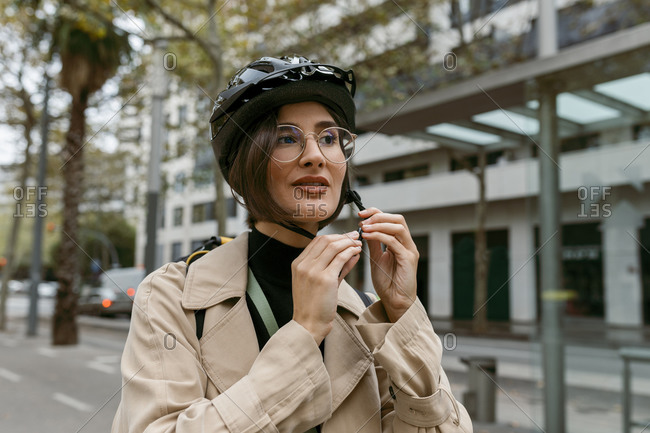 Woman wearing cycling helmet while standing at street in city