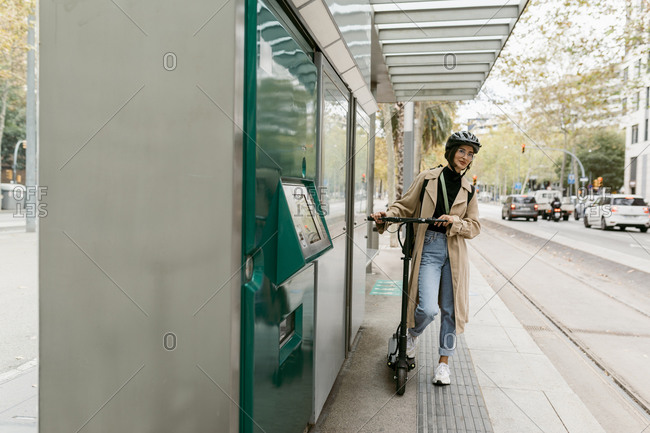 Woman wearing cycling helmet standing with electric push scooter while waiting at tram station in city