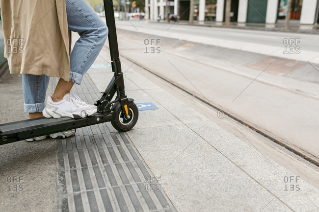 Woman standing with electric push scooter at tram station in city