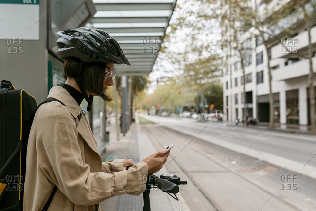 Mid adult woman with instrument case and electric push scooter using mobile phone while standing at tram station in city