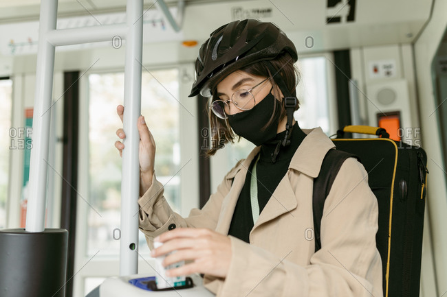 Woman wearing face mask and cycling helmet putting validating ticket in machine while inside tram