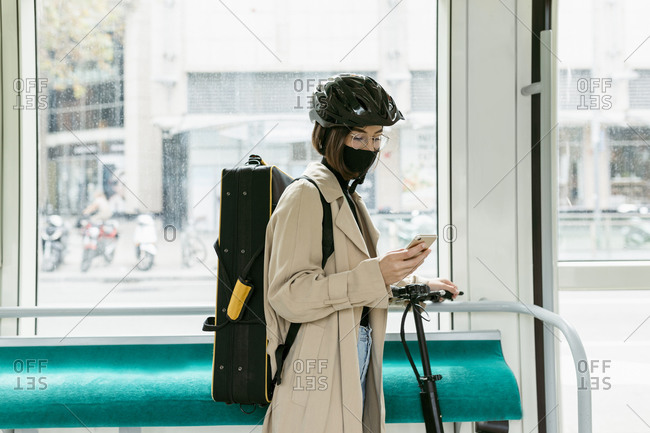 Woman with instrument bag and push scooter using mobile phone while standing in tram
