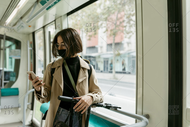 Woman with electric push scooter and face mask using mobile phone while standing in tram