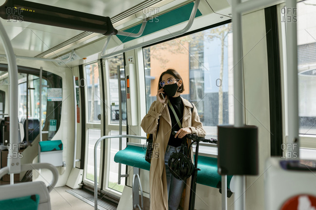 Woman with electric push scooter and face mask talking on mobile phone while standing in tram