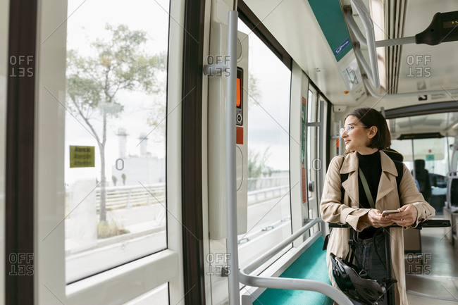Woman with electric push scooter looking away while mobile phone in tram