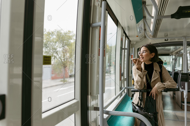 Woman with electric push scooter looking away while talking on mobile phone in tram