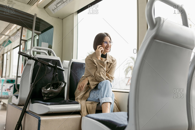 Smiling woman talking on mobile phone while sitting with electric push scooter in tram