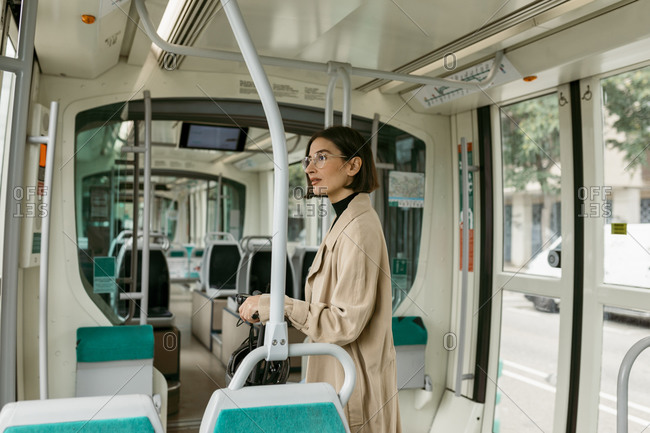 Woman looking away while standing with push scooter in tram