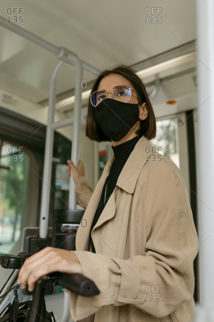 Mid adult woman wearing face mask standing with push scooter in tram