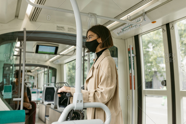 Mid adult woman wearing face mask looking away while traveling with electric push scooter in tram