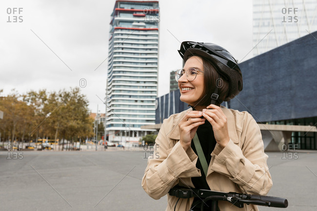 Smiling woman wearing cycling helmet while standing on road in city