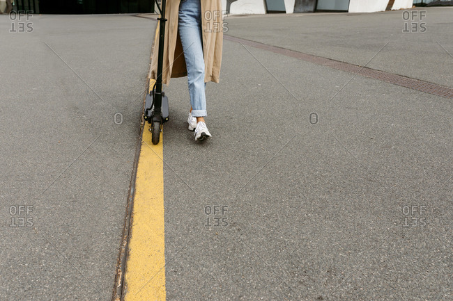 Woman walking with electric push scooter on road marking