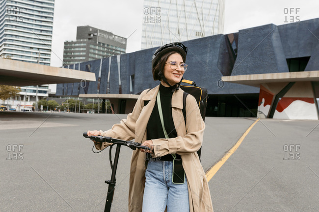 Smiling woman wearing cycling helmet looking away while walking with electric push scooter at city