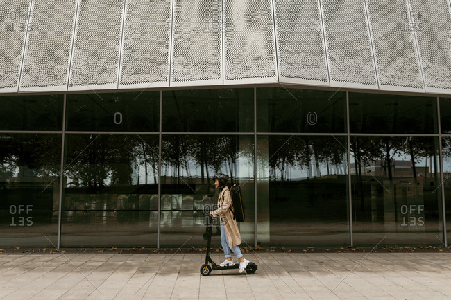 Woman riding electric push scooter on footpath