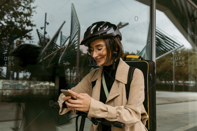 Smiling woman with instrument case and push scooter using mobile phone while standing against glass wall