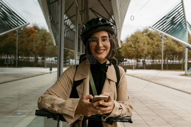 Smiling woman wearing cycling helmet standing with electric push scooter on footpath