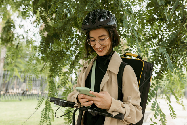 Smiling woman with instrument case and electric push scooter using mobile phone while standing under tree at park