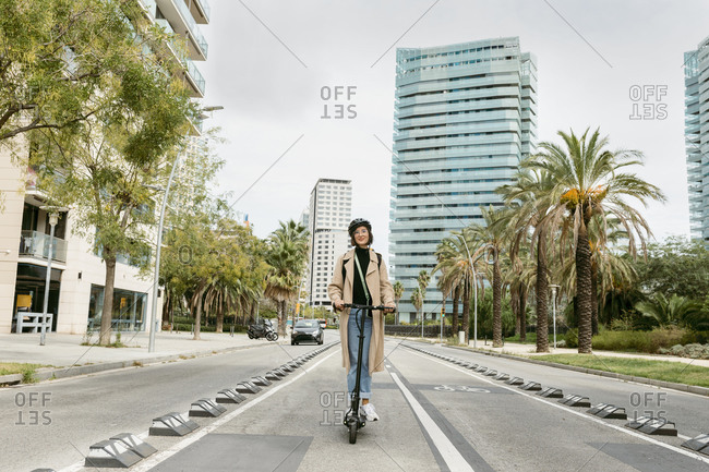 Woman riding electric push scooter on road at city