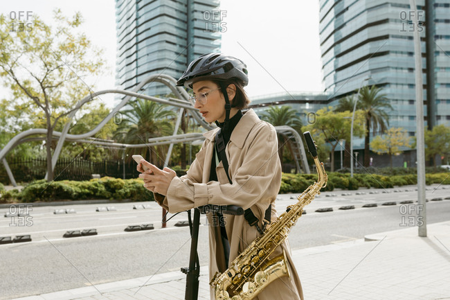 Woman with saxophone using mobile phone while standing on push scooter at city