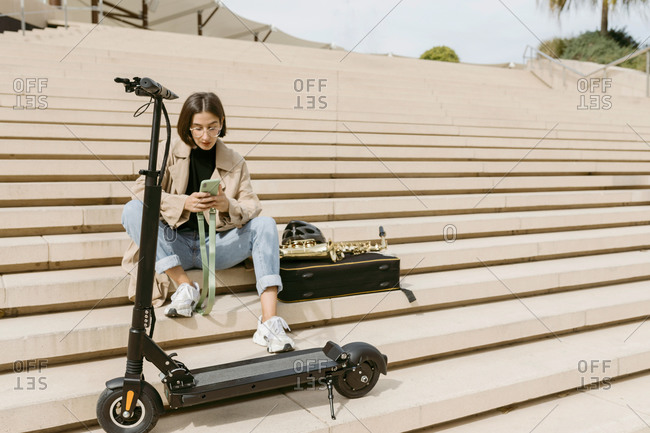 Mid adult woman using mobile phone while sitting by electric push scooter on staircase
