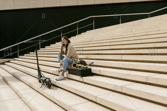 Woman talking on mobile phone while sitting by saxophone instrument and electric push scooter on staircase